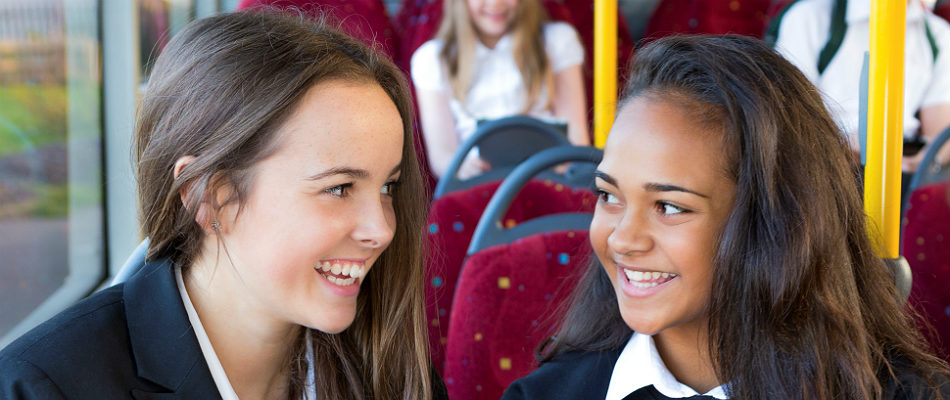 Two pupils smiling at each other on a bus