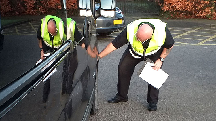 A monitoring and compliance officer inspects a vehicle